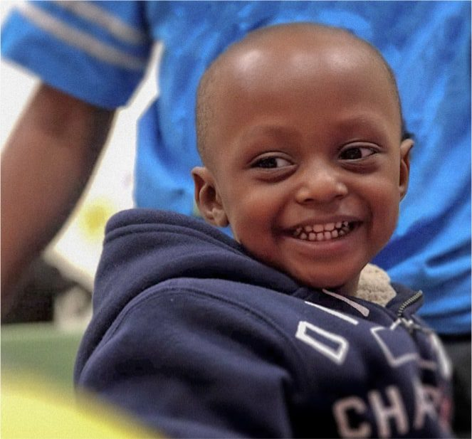 A little boy wearing a navy blue jacket while smiling.