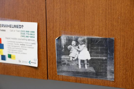 A closeup of an old image of two toddlers sitting on the steps of a home, that is taped to a cupboard in a doctors office.