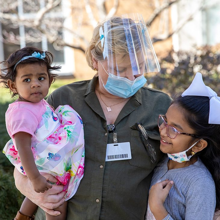 A female specialist is wearing a mask while holding a toddler in her arms in one hand while looking down and holding a young girl next to her.